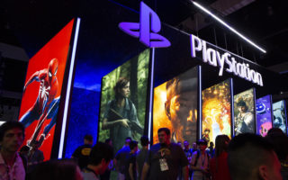 Attendees pass signage for Sony Corp. PlayStation video games during the E3 Electronic Entertainment Expo in Los Angeles, California, U.S., on Tuesday, June 12, 2018. For three days, leading-edge companies, groundbreaking new technologies and never-before-seen products is showcased at E3. Photographer: Troy Harvey/Bloomberg via Getty Images