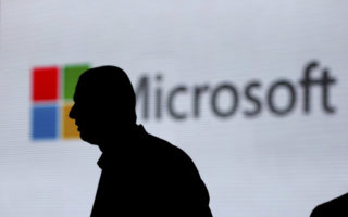 An unidentified man is silhouetted as he walks in front of Microsoft logo at an event in New Delhi, India, Tuesday, Nov. 7, 2017. (AP Photo/Altaf Qadri)