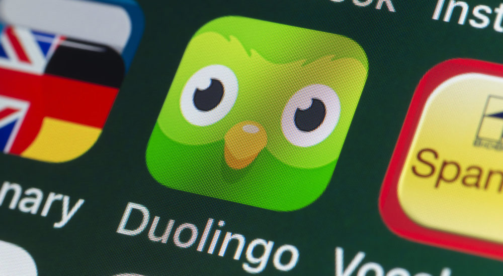 London, UK - July 31, 2018: The buttons of the streaming app Duolingo, surrounded by Dictionary, Vocabulary, Facebook and other apps on the screen of an iPhone.