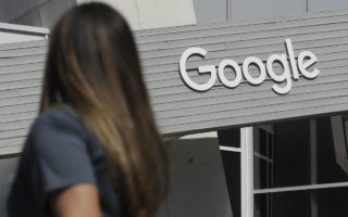 A woman walks below a Google sign on the campus in Mountain View, Calif., Tuesday, Sept. 24, 2019. (AP Photo/Jeff Chiu)