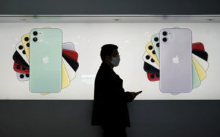 A man wearing a mask walks past an Apple Store in Hong Kong, Wednesday, Feb. 19, 2020. Russia says it will temporarily ban Chinese nationals from entering the country amid the outbreak of the new virus centered in China that has infected more than 73,000 people. (AP Photo/Kin Cheung)